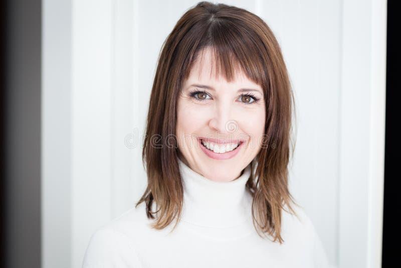 Retrato de una mujer bonita que sonríe en la cámara aislada en blanco fotografía de archivo libre de regalías