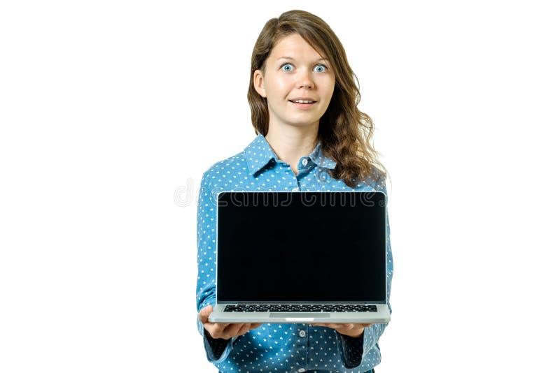 Retrato de una mujer casual feliz que muestra el ordenador portátil en blanco s foto de archivo