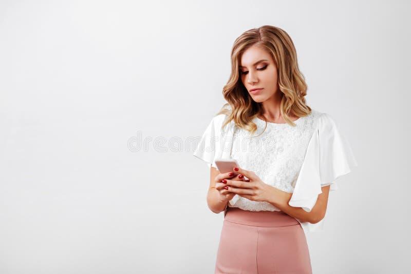 Retrato de una mujer casual sonriente que sostiene smartphone imagen de archivo libre de regalías