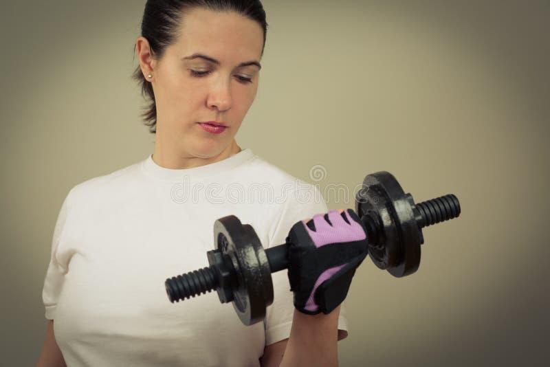 Retrato de una mujer caucásica blanca que sostiene el primer pesado de las pesas de gimnasia del hierro imagen de archivo libre de regalías