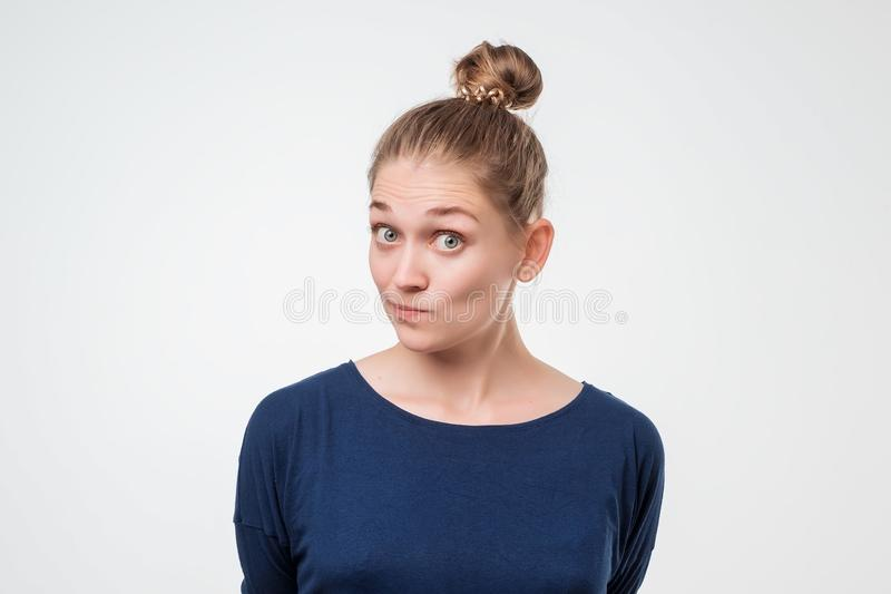 Retrato de una mujer caucásica hermosa en camisa azul interesada en algo imagen de archivo libre de regalías