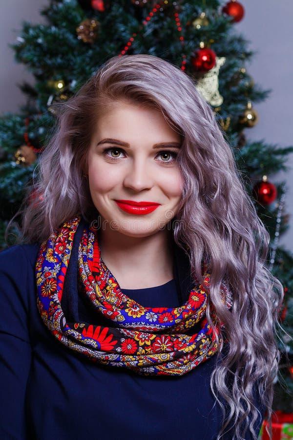 Retrato de una mujer caucásica hermosa que presenta contra el contexto del árbol de navidad fotos de archivo