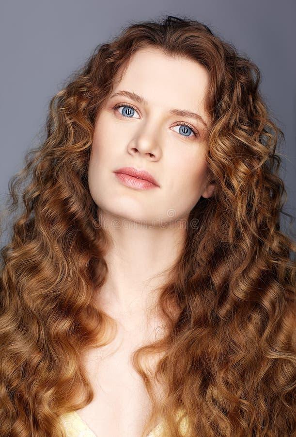 Retrato de una mujer caucásica joven con el pelo ondulado de oro largo fotos de archivo libres de regalías