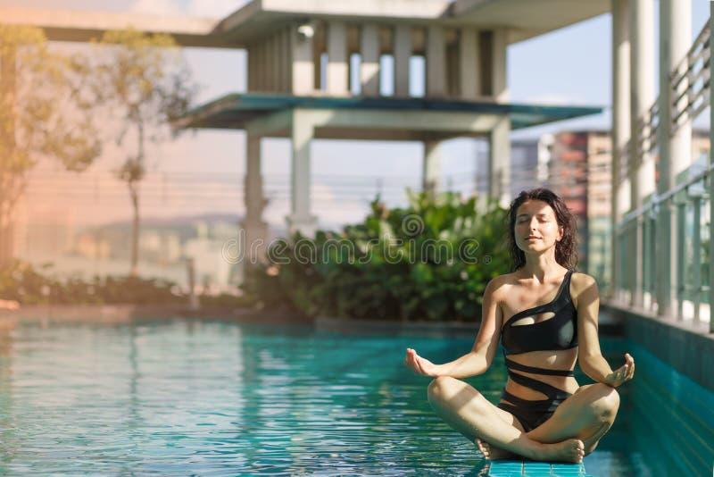 Retrato de una mujer caucásica de la meditación atractiva en un traje de baño que se sienta en actitud del loto al borde de una p fotografía de archivo libre de regalías