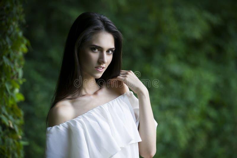 Retrato de una mujer caucásica sonriente feliz hermosa en el vestido blanco con los hombros abiertos, la piel limpia, el pelo lar fotos de archivo