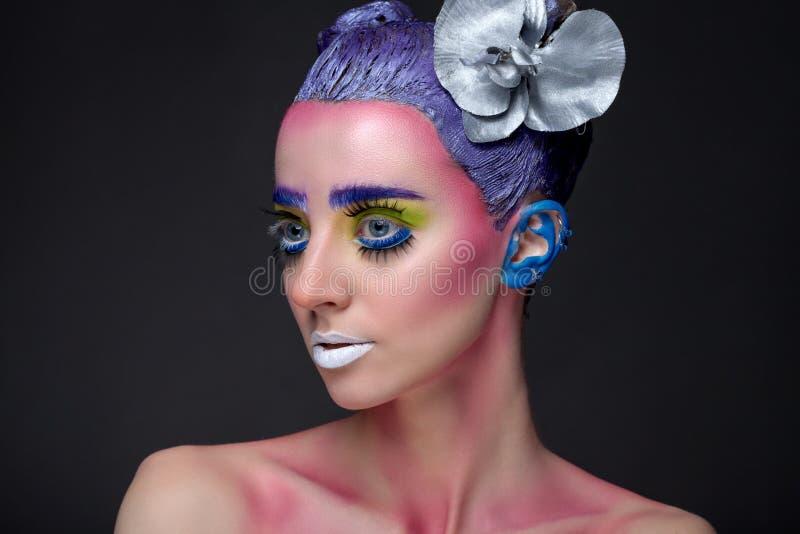 Retrato de una mujer con maquillaje creativo en un fondo fotos de archivo