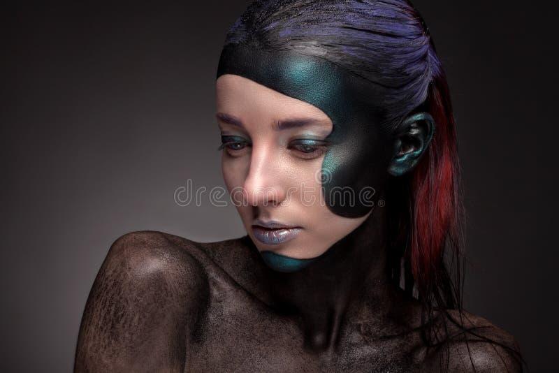 Retrato de una mujer con maquillaje creativo en un fondo gris imagen de archivo libre de regalías