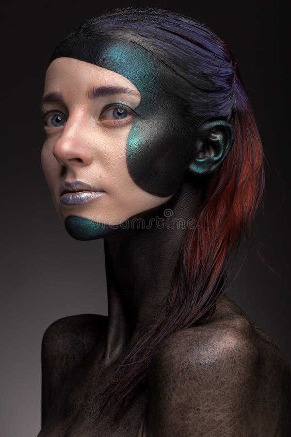 Retrato de una mujer con maquillaje creativo en un fondo gris fotos de archivo libres de regalías
