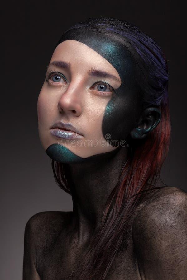 Retrato de una mujer con maquillaje creativo en un fondo gris fotos de archivo