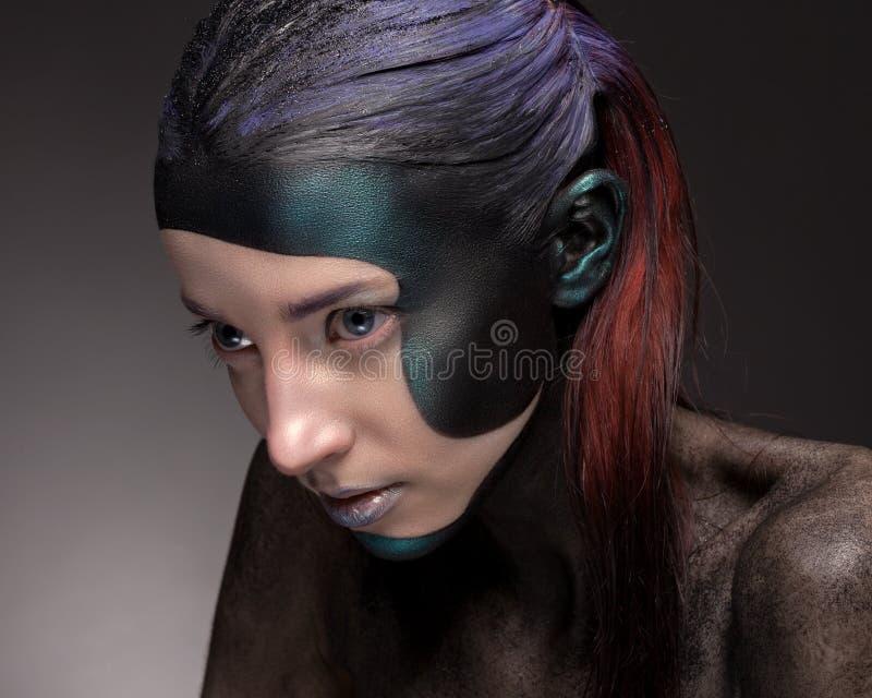 Retrato de una mujer con maquillaje creativo en un fondo gris fotografía de archivo