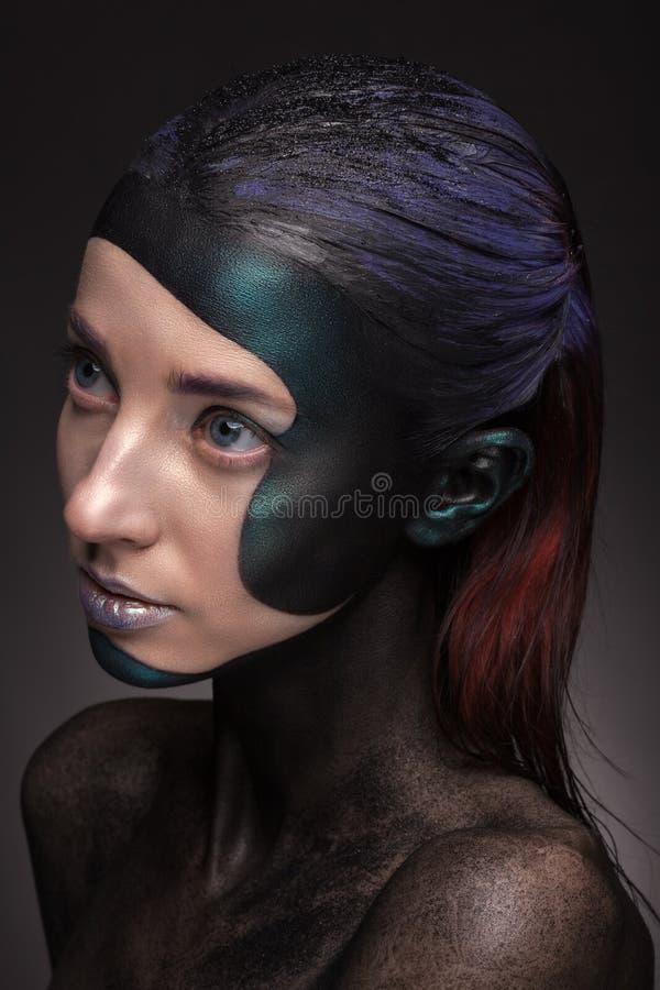 Retrato de una mujer con maquillaje creativo en un fondo gris foto de archivo libre de regalías