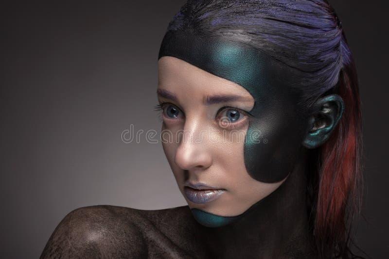 Retrato de una mujer con maquillaje creativo en un fondo gris foto de archivo