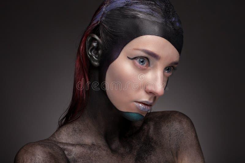 Retrato de una mujer con maquillaje creativo en un fondo gris imágenes de archivo libres de regalías