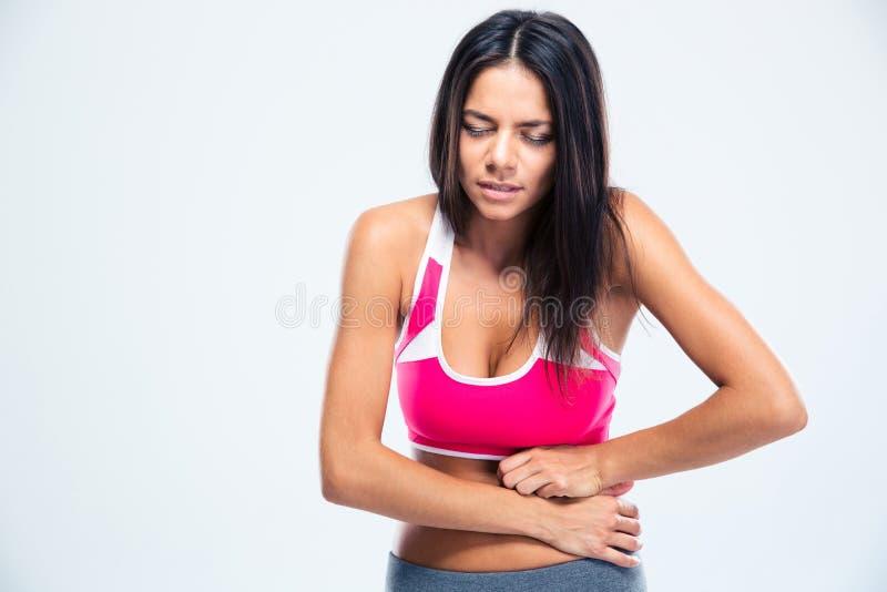 Retrato de una mujer de la aptitud con dolor de estómago fotografía de archivo