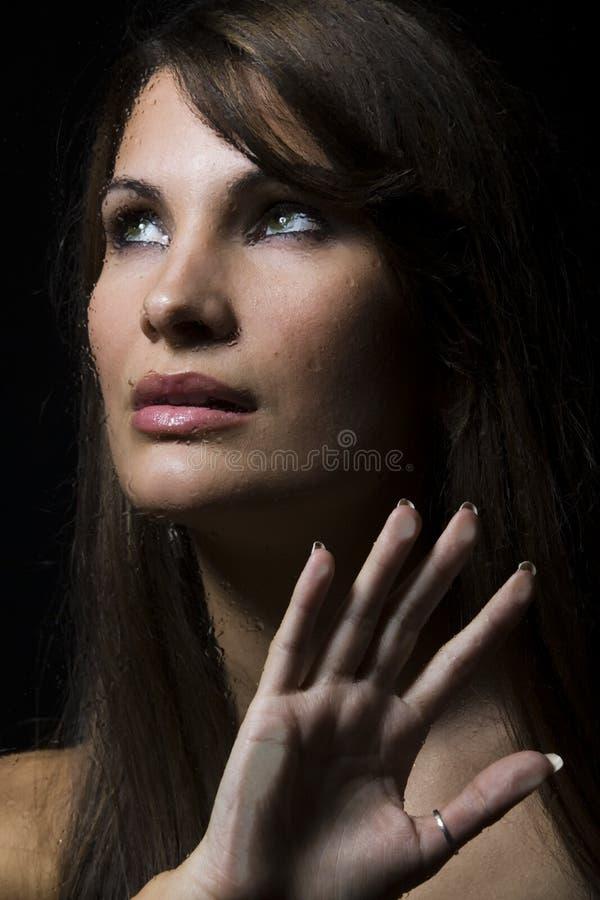 Retrato de una mujer detrás del vidrio mojado imagenes de archivo