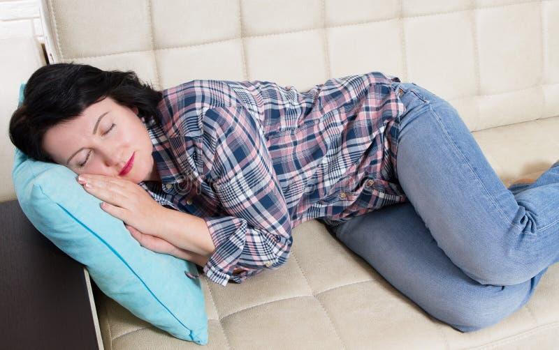 Retrato de una mujer durmiente que se relaja en un sofá después del trabajo en casa que miente en un sofá en la sala de estar en  imagen de archivo libre de regalías