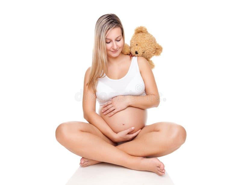 Retrato de una mujer embarazada que se sienta en piso y que sostiene el vientre imagenes de archivo