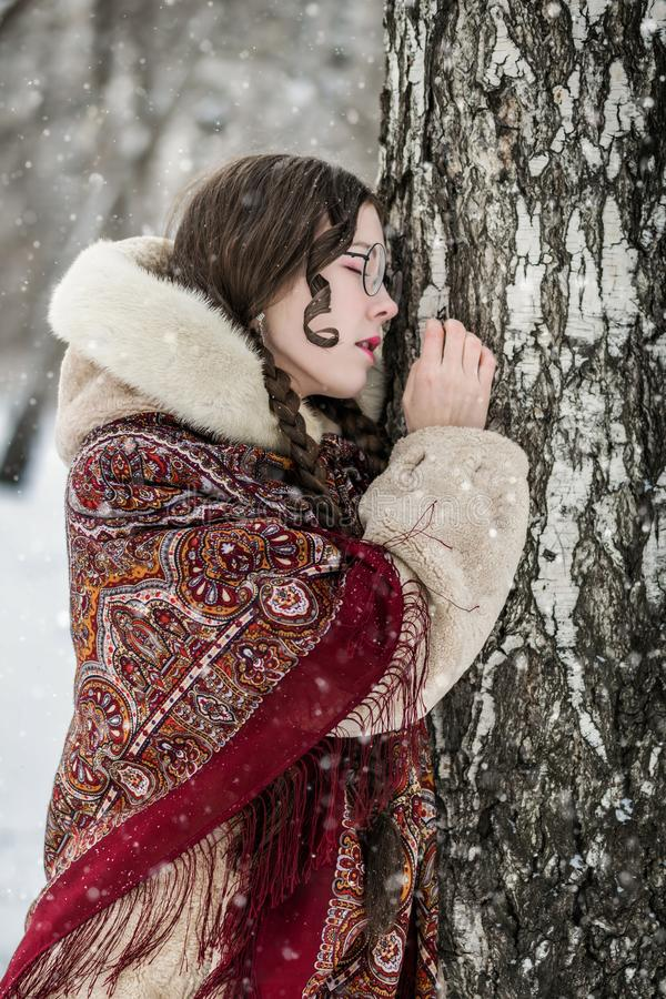 Retrato de una mujer en un abrigo de pieles cerca de un abedul fotografía de archivo libre de regalías