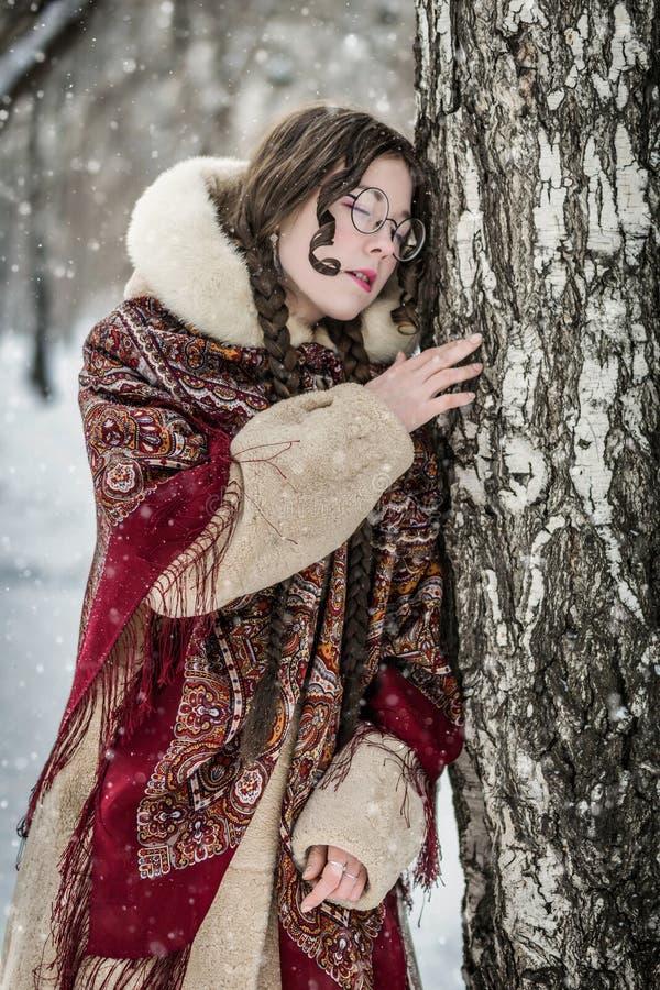 Retrato de una mujer en un abrigo de pieles cerca de un abedul imagen de archivo