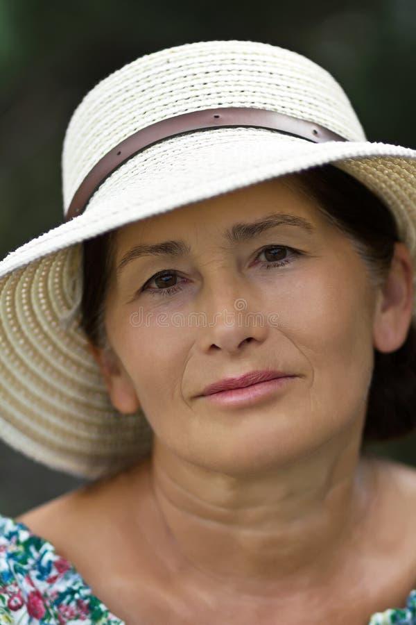 Retrato de una mujer en un sombrero de paja imagenes de archivo