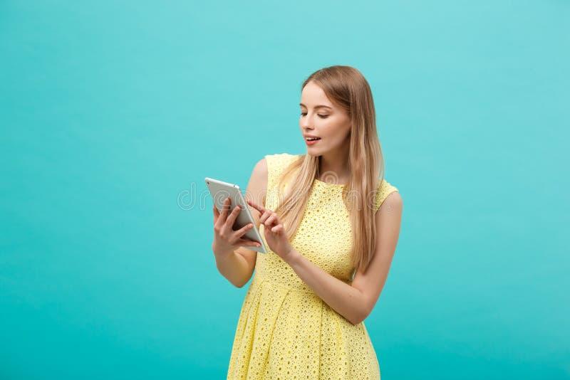 Retrato de una mujer feliz joven que sostiene la tableta con el espacio de la copia mientras que se coloca aislado sobre fondo az imagen de archivo
