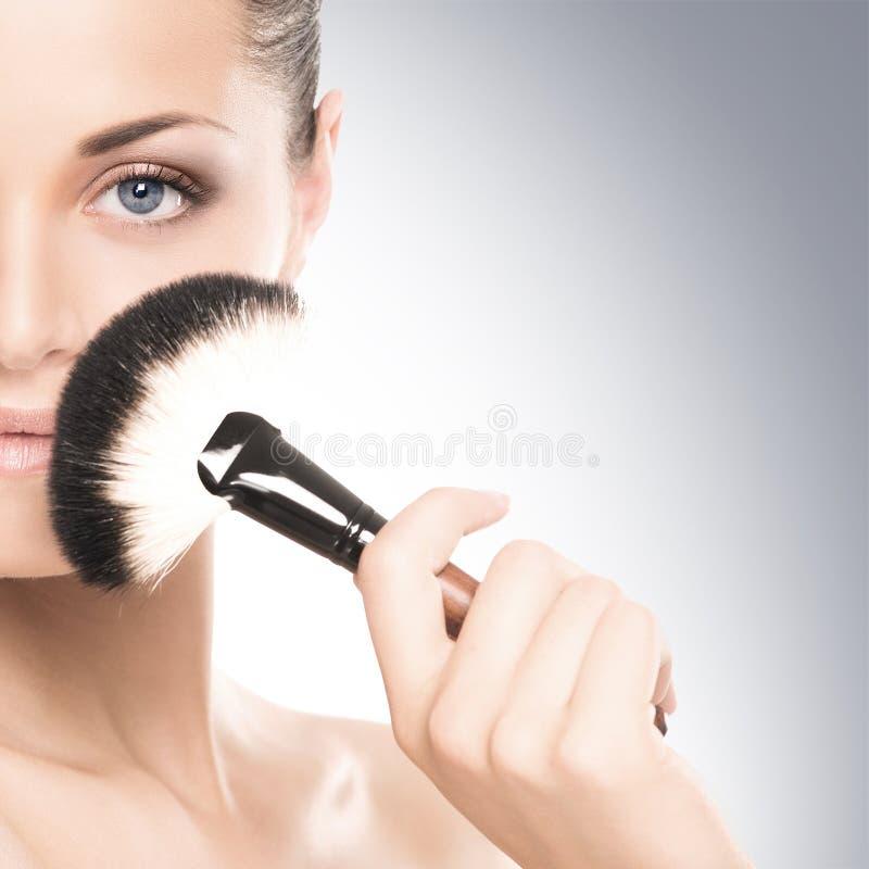 Retrato de una mujer feliz que sostiene un cepillo del maquillaje fotografía de archivo libre de regalías