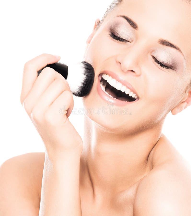 Retrato de una mujer feliz que sostiene un cepillo del maquillaje fotos de archivo libres de regalías