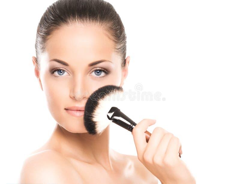 Retrato de una mujer feliz que sostiene un cepillo del maquillaje imagen de archivo libre de regalías