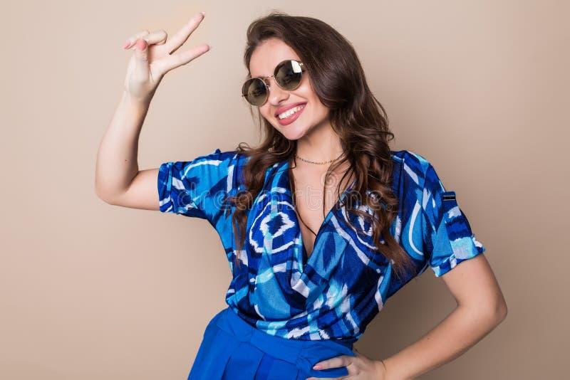 Retrato de una mujer feliz sonriente del playfull en las gafas de sol que muestran la muestra de la victoria y que miran la cámar foto de archivo libre de regalías