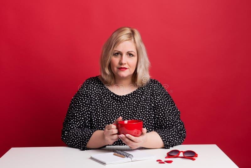 Retrato de una mujer gorda atractiva en estudio en un fondo rojo foto de archivo