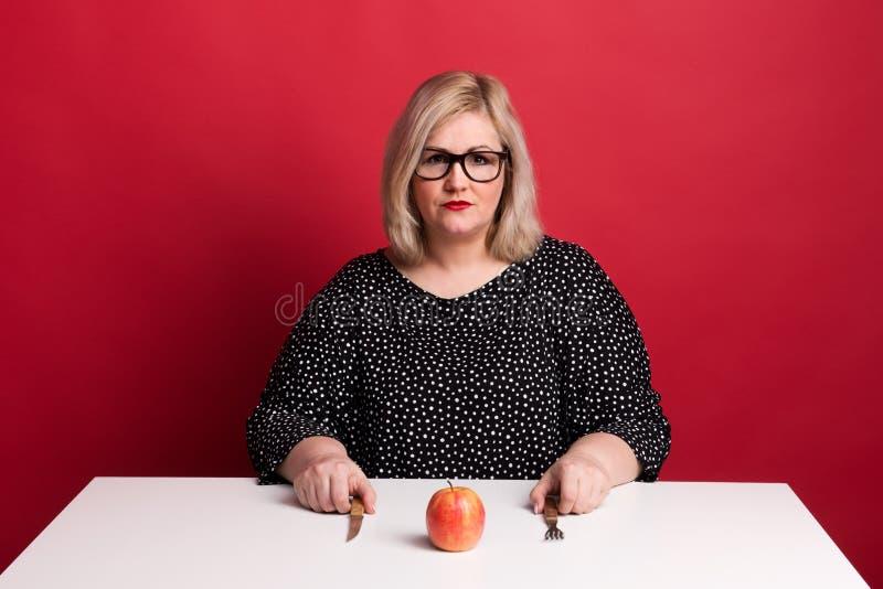 Retrato de una mujer gorda atractiva triste con una manzana en estudio fotografía de archivo