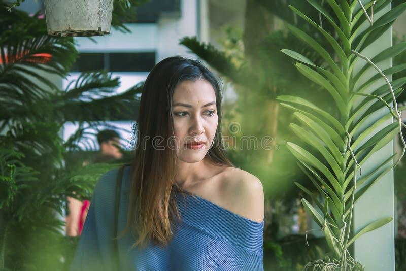 Retrato de una mujer hermosa bajo mirada de las hojas foto de archivo