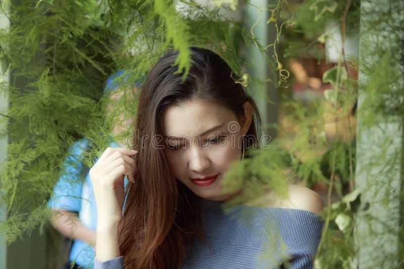 Retrato de una mujer hermosa bajo mirada de las hojas fotografía de archivo