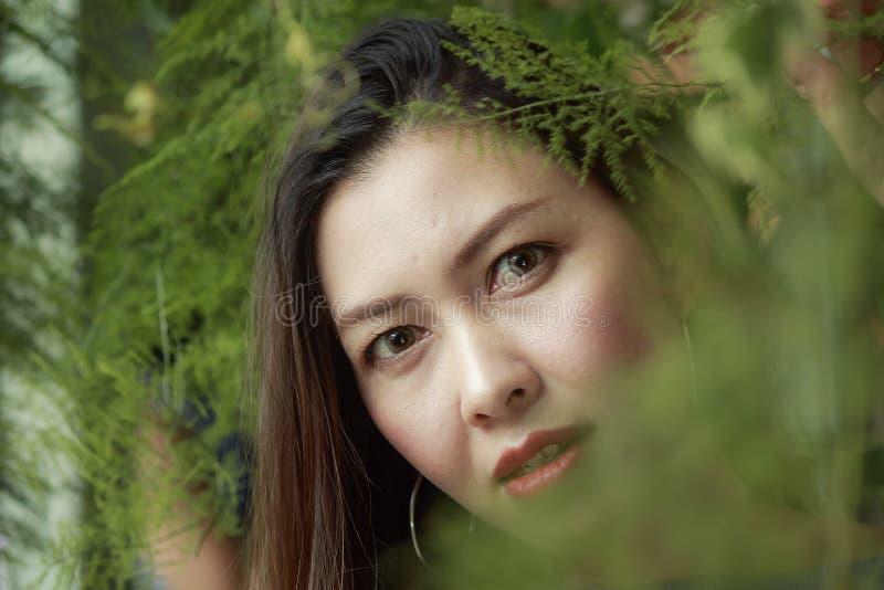 Retrato de una mujer hermosa bajo mirada de las hojas imagen de archivo libre de regalías