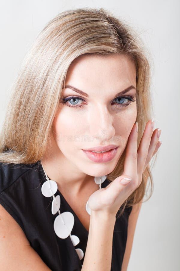 Retrato de una mujer hermosa con el pelo blanco Una mujer toca su cara fotos de archivo