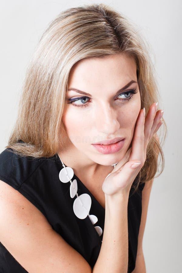 Retrato de una mujer hermosa con el pelo blanco Una mujer toca su cara imagen de archivo libre de regalías