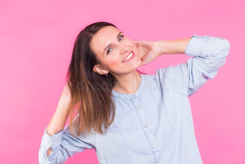 Retrato de una mujer hermosa con el pelo marrón largo que lleva la blusa azul del algodón, cintura derecha para arriba sonriendo  fotos de archivo libres de regalías