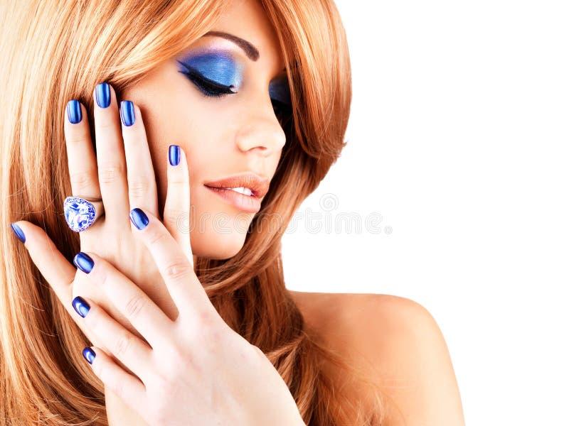 Retrato de una mujer hermosa con los clavos azules, maquillaje azul fotos de archivo