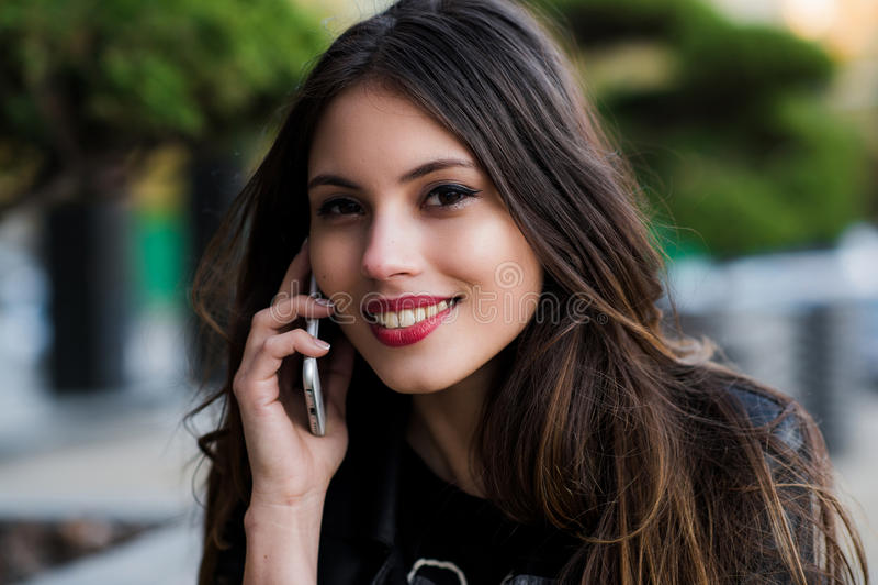 Retrato de una mujer hermosa con sonrisa blanca perfecta que habla en el teléfono móvil al aire libre fotos de archivo