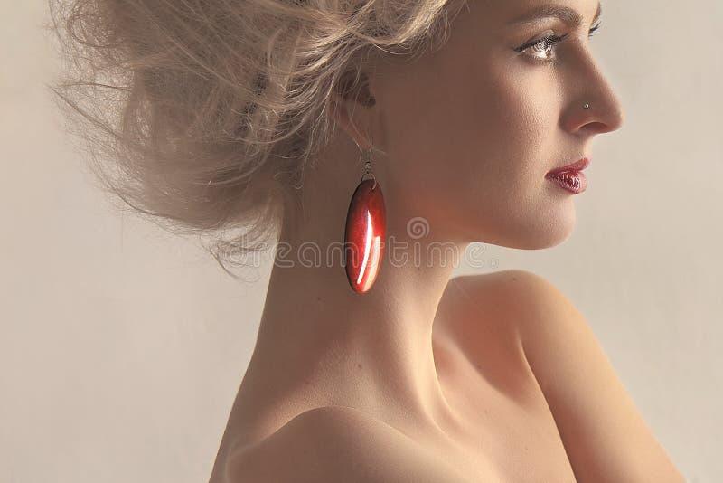 Retrato de una mujer hermosa con un pendiente en a foto de archivo libre de regalías