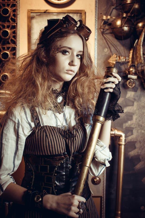 Retrato de una mujer hermosa del steampunk, con un telescopio imagen de archivo libre de regalías