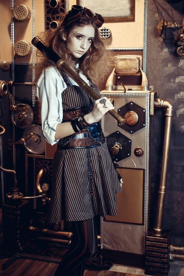 Retrato de una mujer hermosa del steampunk, con un telescopio en un g imagen de archivo