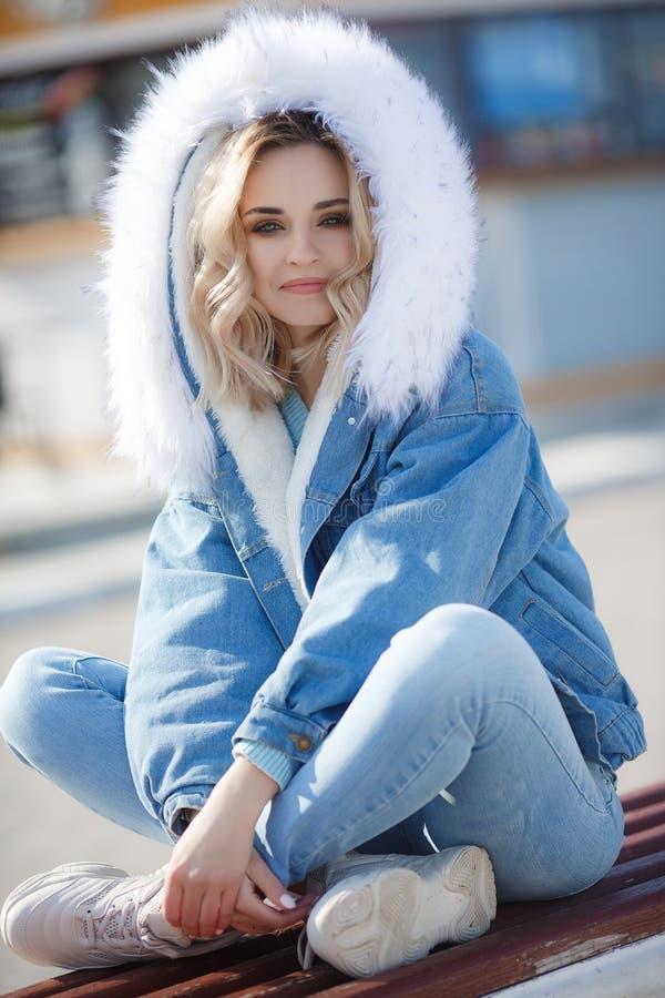 Retrato de una mujer hermosa en un aire libre de la chaqueta azul en primavera temprana en la costa del oc?ano fotografía de archivo
