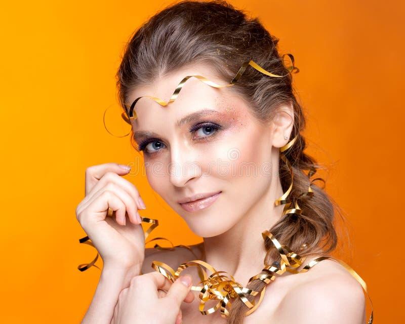 Retrato de una mujer hermosa en un fondo anaranjado foto de archivo libre de regalías