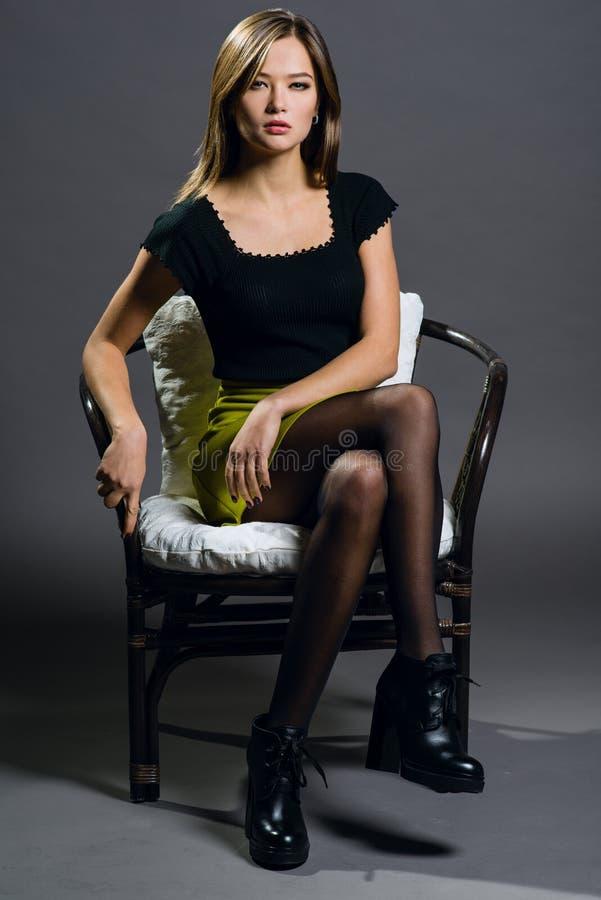 Retrato de una mujer hermosa en un fondo oscuro, que sienta o fotos de archivo libres de regalías