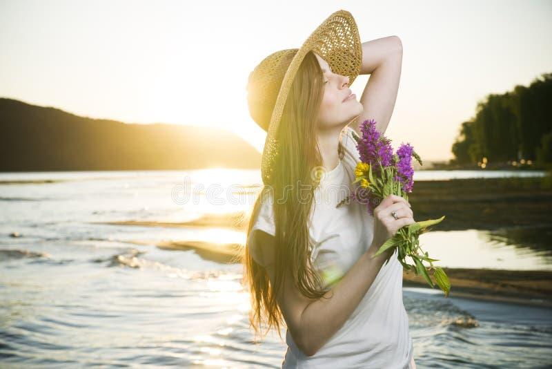 Retrato de una mujer hermosa en un sombrero en un fondo de una puesta del sol foto de archivo libre de regalías