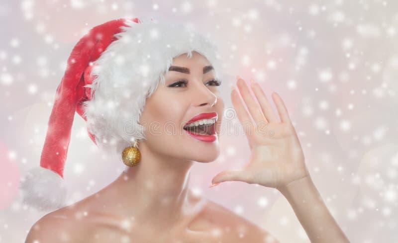 Retrato de una mujer hermosa en un sombrero rojo de Santa Claus en fondo de los copos de nieve fotos de archivo