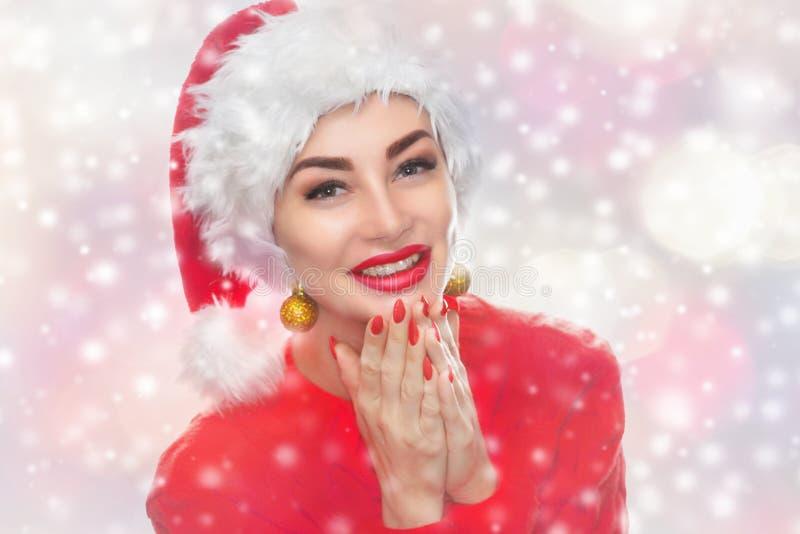Retrato de una mujer hermosa en un sombrero rojo de Santa Claus y un suéter rojo hecho punto en fondo de los copos de nieve fotos de archivo libres de regalías
