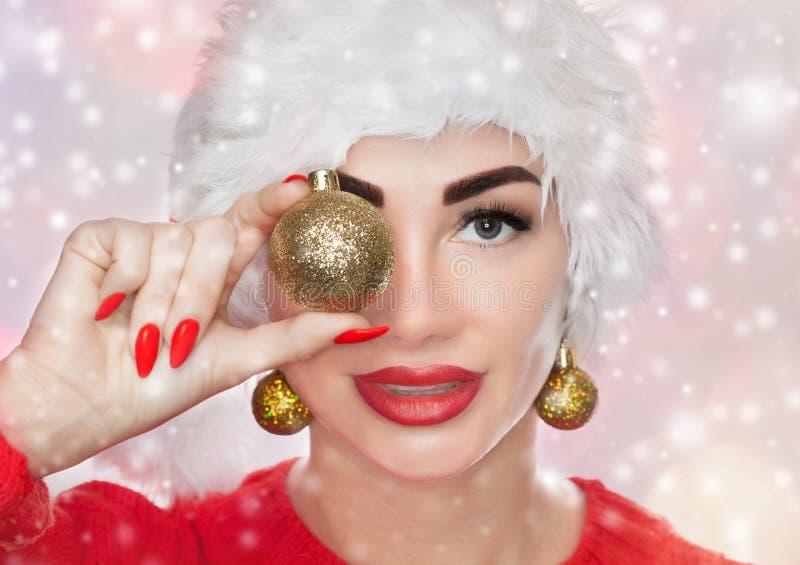 Retrato de una mujer hermosa en un sombrero rojo de Santa Claus y un suéter rojo hecho punto que retienen una bola de oro de la N fotos de archivo libres de regalías