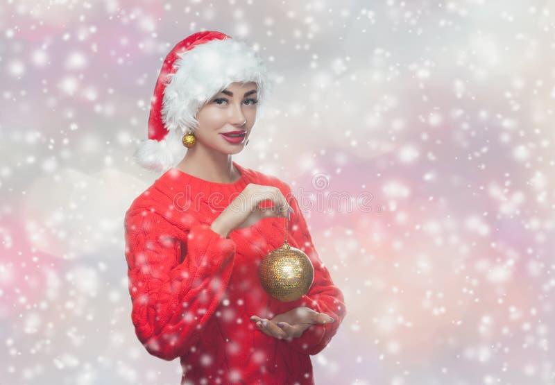 Retrato de una mujer hermosa en un sombrero rojo de Santa Claus y un suéter rojo hecho punto que sostienen una bola de oro de la  imagen de archivo